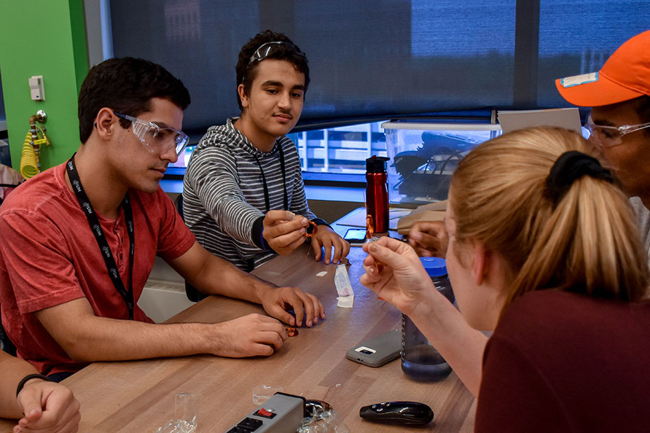 While participating in Steven Leeb's direct-current motor lab activity, freshmen Dylan Lewis and Jose Domingo Soto Rivera compare rotors made using magnet wire with counselor Rebecca Eisenach '19.