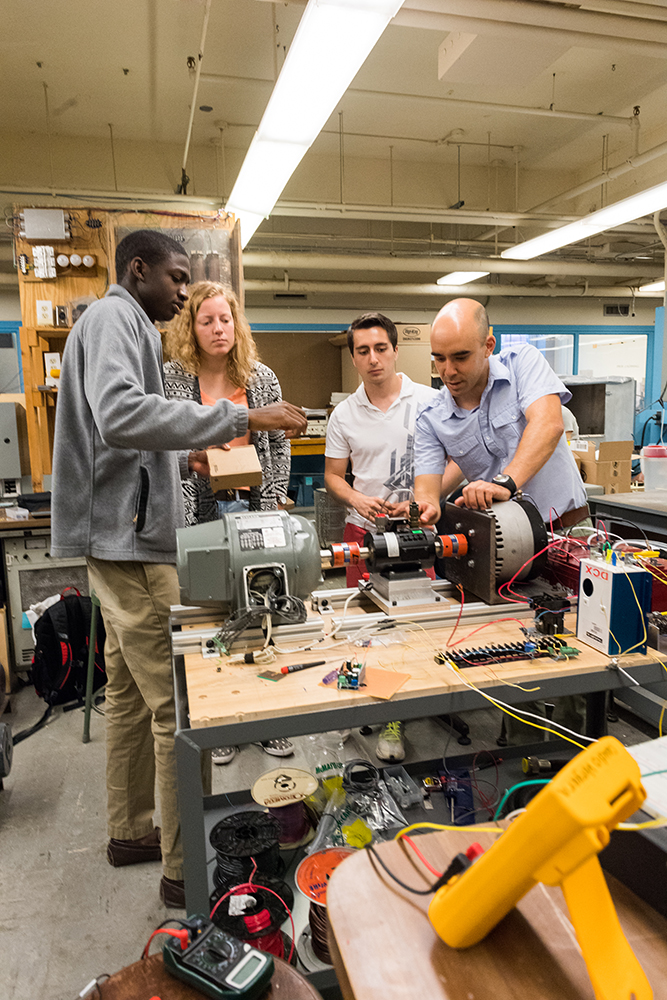 Left to right: UROP students Daniel Vignon '17, Taylor V'Dovec '19, and Juan De Jesus '17, and MITEI postdoc Claudio Vergara adjust a torque and angular speed sensor, which is mounted on a shaft between electrical machines operated as a motor and a generator in their lab-scale model of a power system. The sensor will be used to estimate the electromechanical parameters of the machines. Photo: Justin Knight