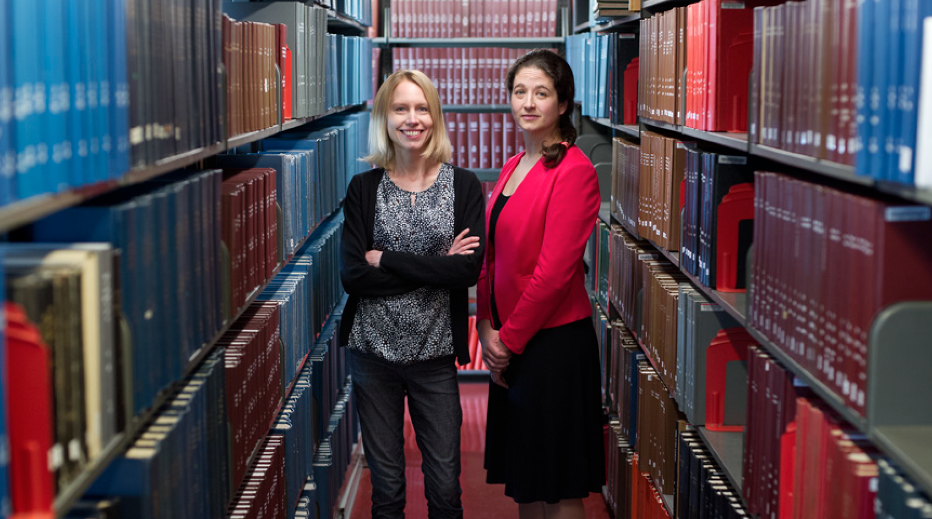 Professor Stefanie Jegelka and Professor Elsa Olivetti stand in a library alley.